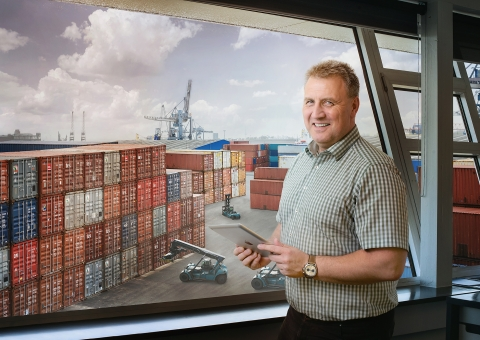 Manager with tablet standing in front of ports
