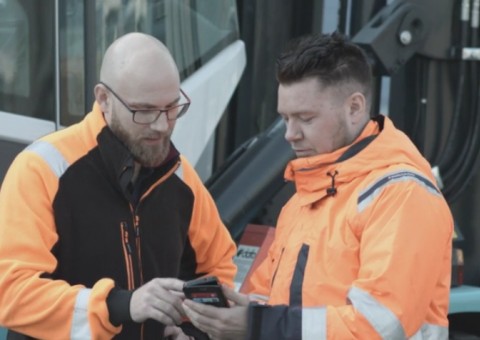 Two workers looking at a phone